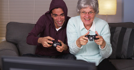 Hispanic grandson and grandmother playing video games