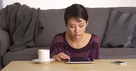 Asian woman sitting at coffee table with tablet