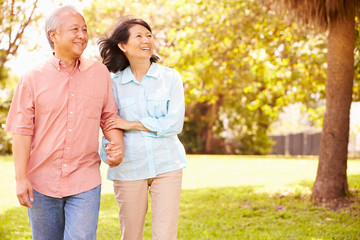 Senior Asian Couple Walking Through Park Together Wall mural