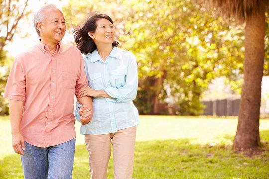 Senior Asian Couple Walking Through Park Together