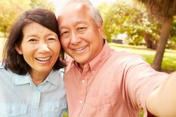 Senior Asian Couple Taking Selfie In Park Together