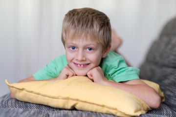 süßer kleiner junge liegt auf dem sofa
