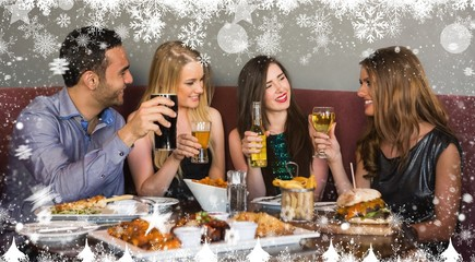 Composite image of happy friends sitting together having dinner