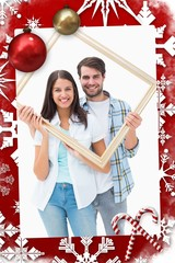 Composite image of happy young couple holding picture frame