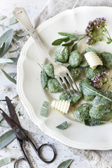 homemade spinach dumplings with sage, butter curls and flowers