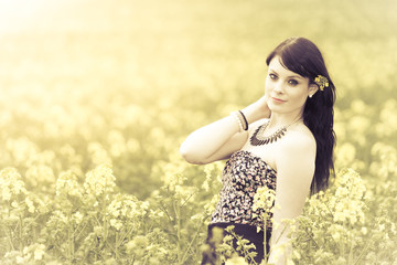 Beautiful woman in meadow of yellow flowers bright environment