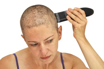 Woman shaving herself bald using left hand, closeup