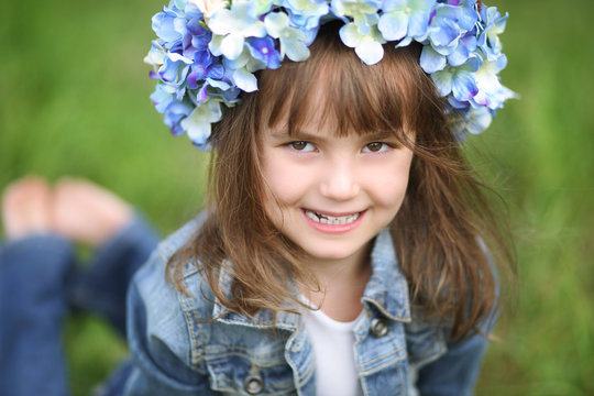 Smiling young girl in a wreath of blue flowers