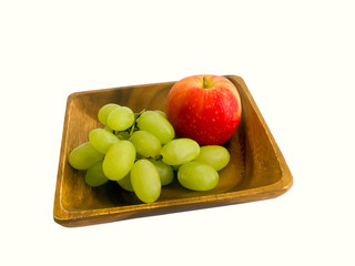 Apple and grapes on a wooden plate