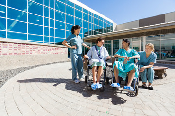 Patients On Wheelchair By Nurses Outside Hospital Building