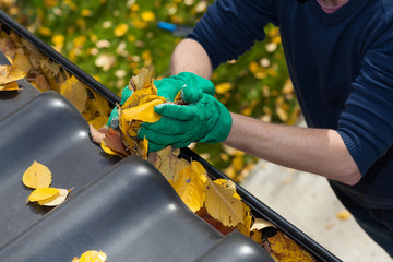 Cleaning the rain gutter during autumn