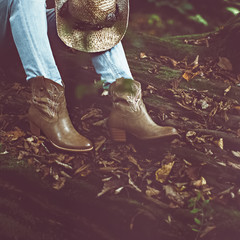 Autumn cowboy style girl. Cowboy boots in the woods