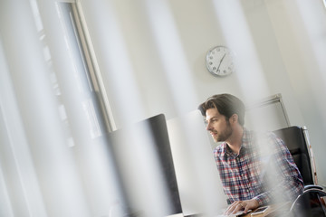 View through an office partition of a man seated at a desk.