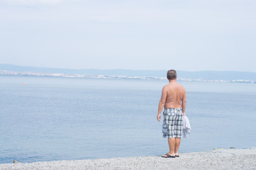 Adult man relaxing  and looking at the sea