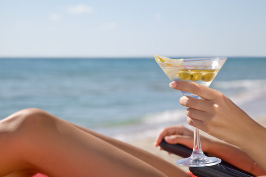 Hand of a girl with a cocktail on the beach