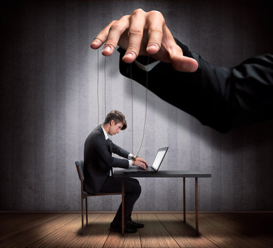 Businessman's hand controlling a worker marionette