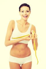 Pretty smiling woman measuring breast