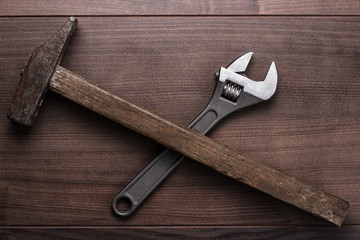 old rusty hammer and wrench on the table