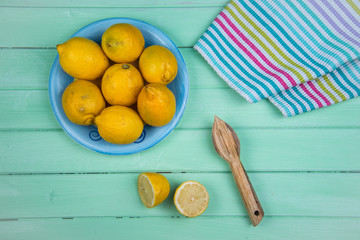 Organic lemons and juice squeezer on table
