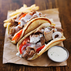 greek gyros with tzatkiki sauce and fries on parchment