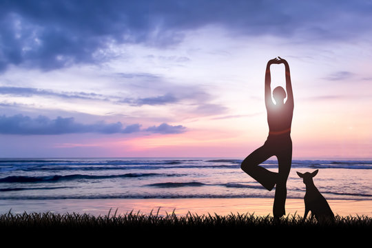 Silhouette of young woman practising yoga on beach at sunset