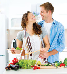 Man and Woman in their Kitchen Preparing Vegetable Salad