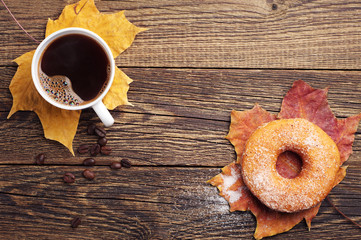 Coffee, donut and autumn leaves