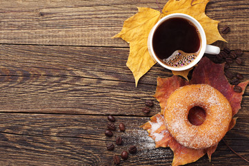 Donut, coffee and autumn leaves
