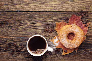 Sweet donut, coffee and autumn leaves