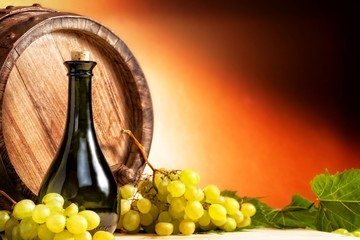 Bottle of wine in front of wine barrel with white grapes.