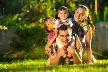Happy young family having fun outdoors in summer garden
