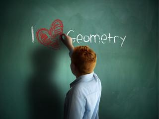 I love Geometry. Schoolboy writing on a chalkboard.