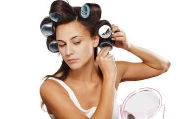 young woman putting curlers in her hair