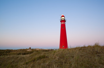 Wall Mural - red lighthouse at sunset on island coast