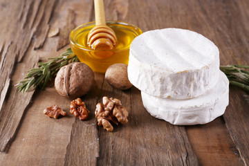 Camembert cheese, nuts and honey in glass bowl