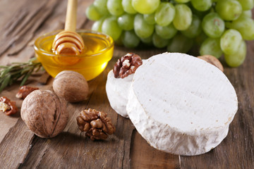 Camembert cheese, nuts, grapes and honey in glass bowl