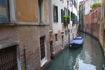 Fototapete - Narrow canal among old brick houses in Venice, Italy.