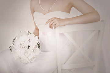 Bride holding wedding bouquet of white peonies