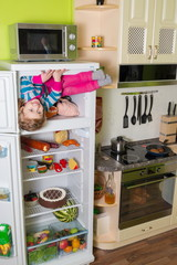 Little girl sits in freezer refrigerator at inverted house