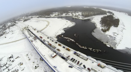 Aerial view to construction on bridge with cars against river