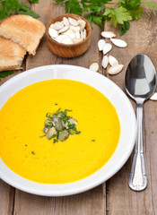 Pumpkin soup on rustic wooden table