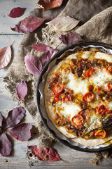 homemade rustic pizza on tray with autumnal leaves