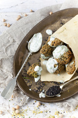 homemade falafel balls with yogurt sauce on paper cornet