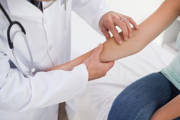 Doctor examining patients arm