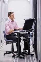 Technician sitting on swivel chair using laptop