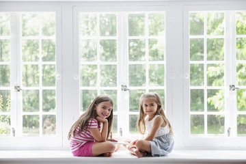Two girls with digital tablet sitting by large window