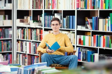 Young man reading in a library