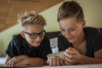 Portrait von zwei Jungen, mit Smartphone auf dem Bett