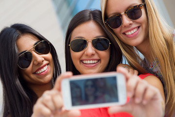 Three friends taking photos with a smartphone