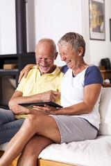 Senioren sitzen auf der Couch mit Tablet-PC